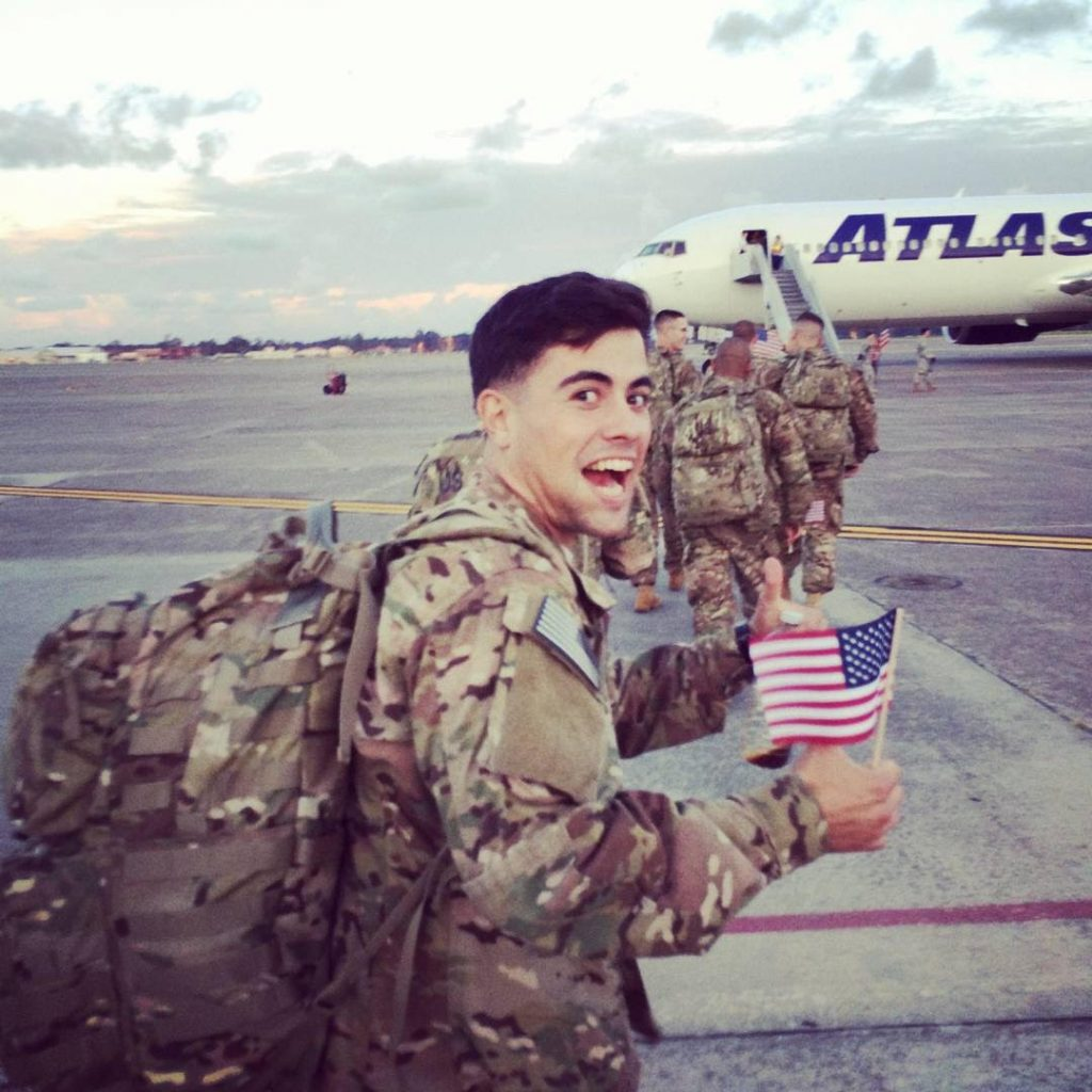 man in military uniform waving American flag in front of airplane