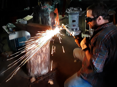 man using torch on metal pieces