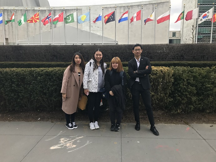 four students standing outside in front of row of international flags