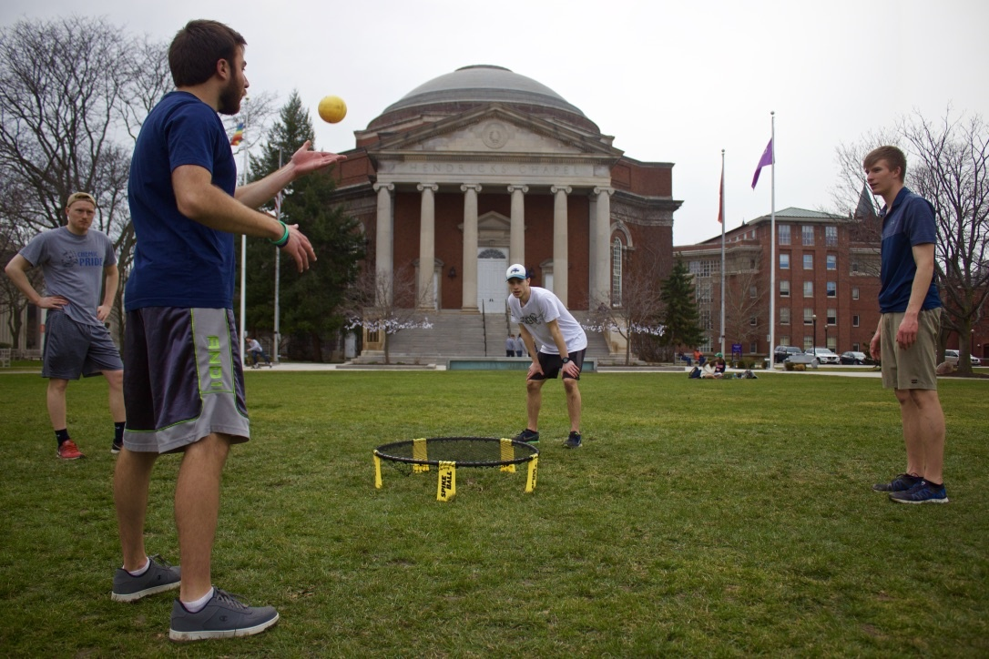man tossing ball surrounded by three other men on Quad