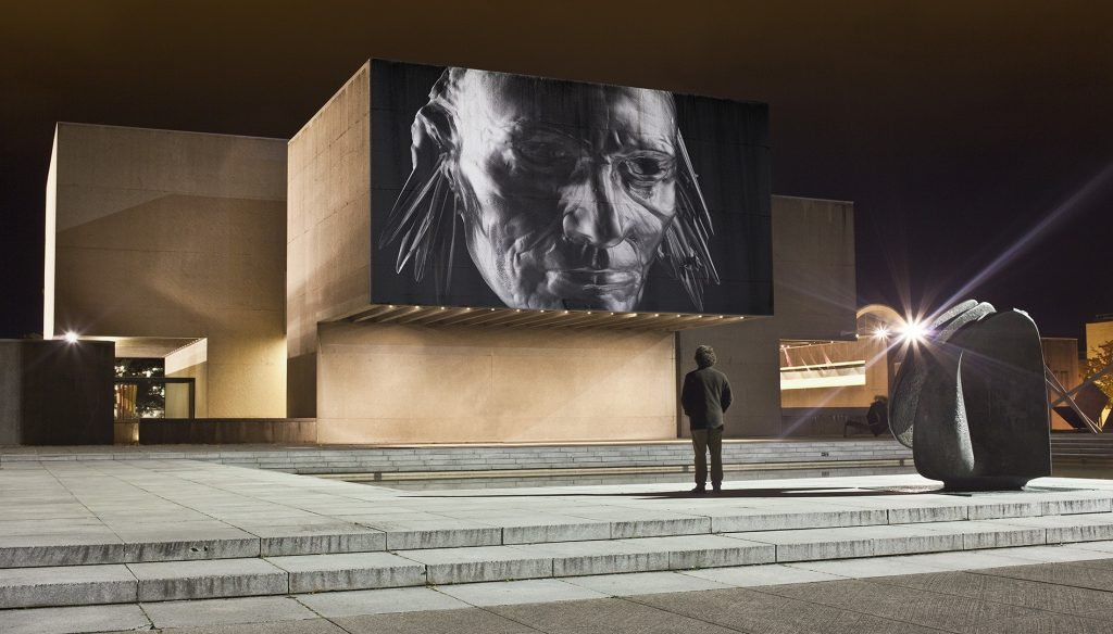 man looking at video projected on side of Everson Museum