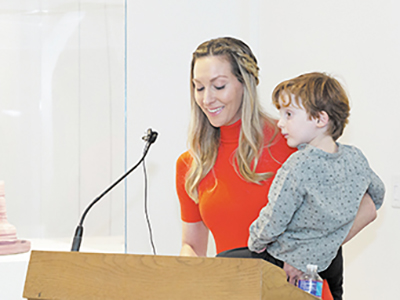 woman standing at a podium holding a young boy