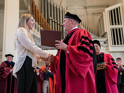 woman receiving certificate from man in academic rob