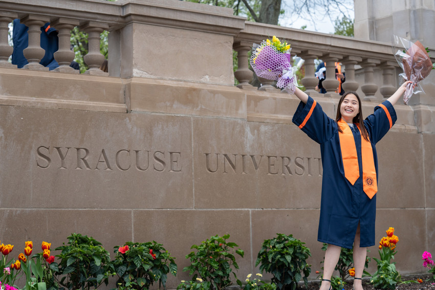 woman in graduation gown standing in front of Syracuse University sign etched in stone