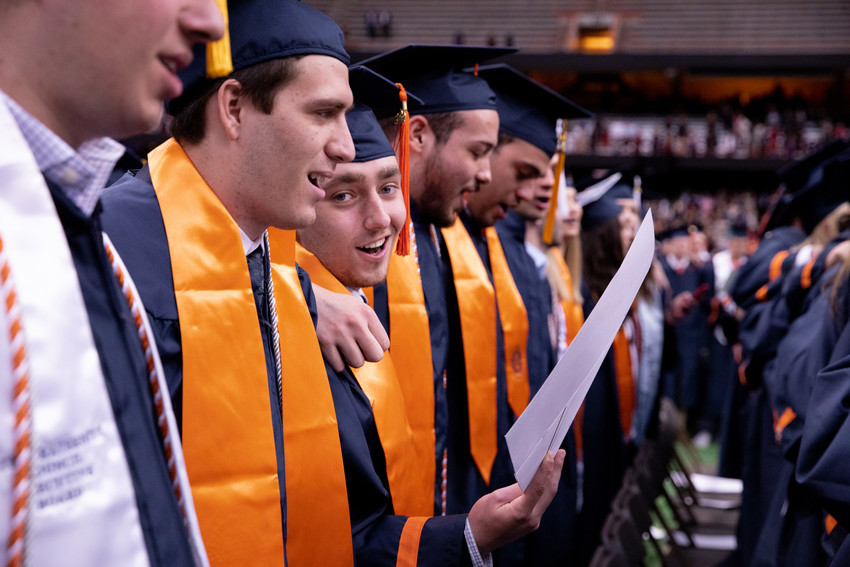 row of graduates singing