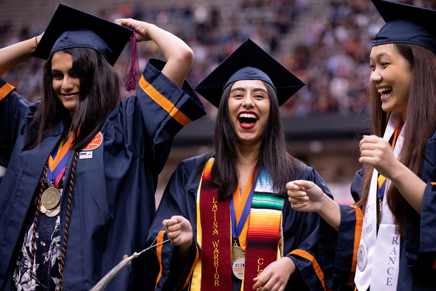 three women graduates laughing