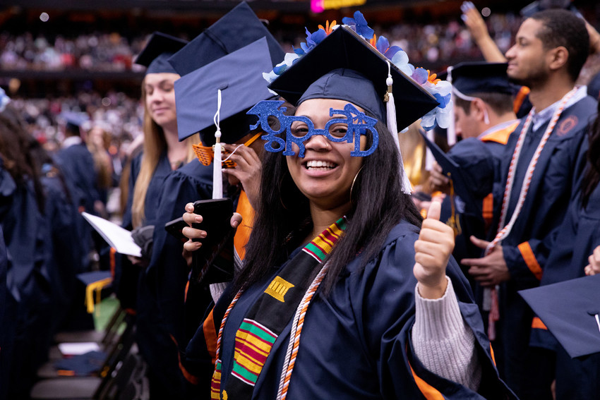 woman in graduation cap and gown among other graduates