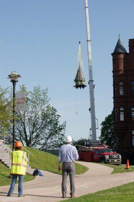 workers on the ground watching cupola being lowered