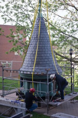 Workers inspect the cupola on the ground