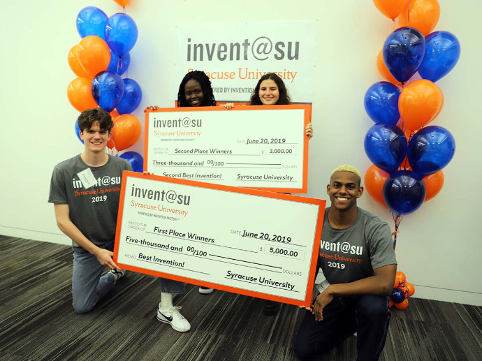 four people holding two oversized checks