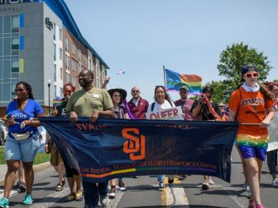 Syracuse University members march with others in higher education at CNY Pride Parade, holding Syracuse University LGBT Resource Center banner