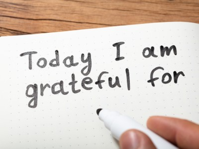 Person signing a note that says Today I am Grateful for.