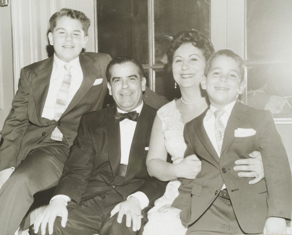 two boys sitting with two adults