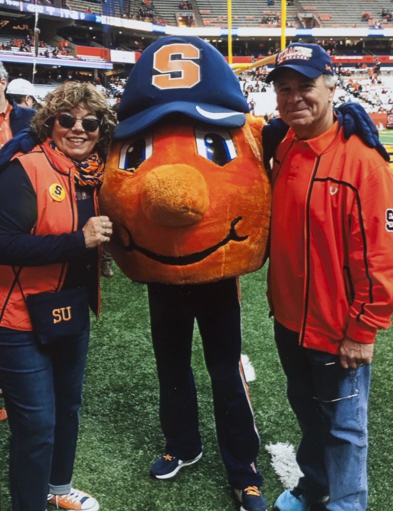 a woman and man standing with Otto the Orange mascot