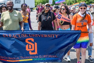Folks marching in Pride Parade holding Syracuse University LGBT Resource Center banner, wearing Syracuse University apparel and holding Syracuse University flag