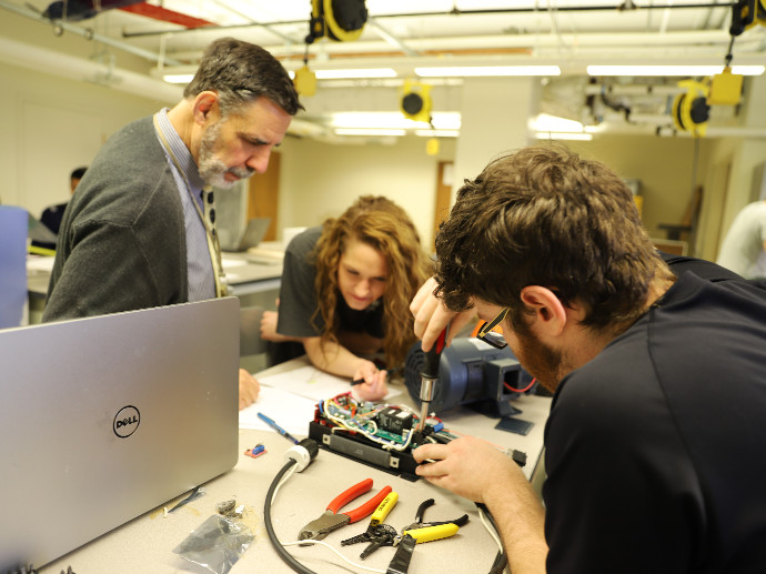 three people working with tools on electrical component