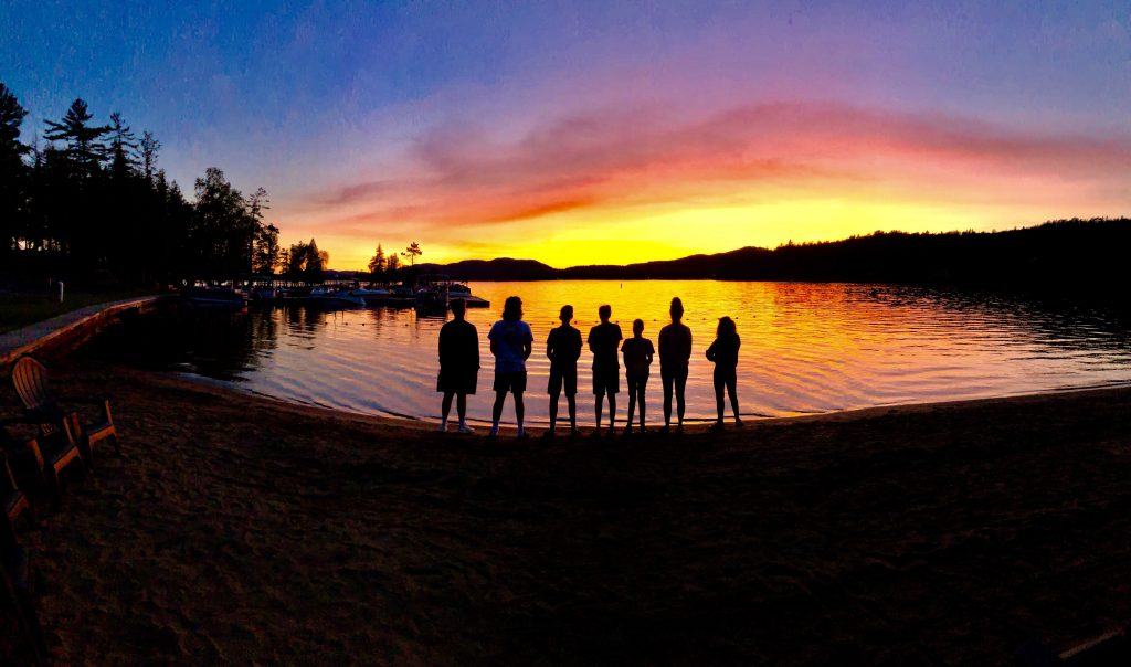 group of children at water's edge at sunset