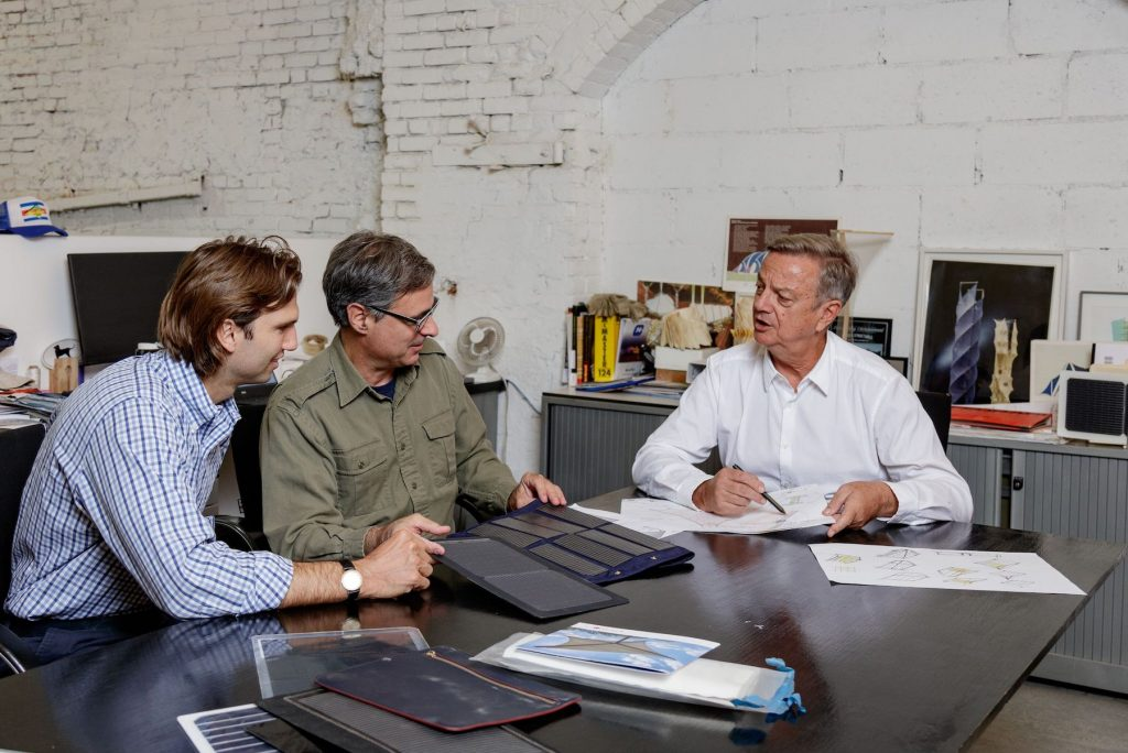 Three men sitting at a table looking at fabric