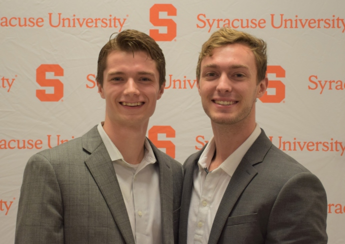 Two young men in suits in front of a Syracuse University banner