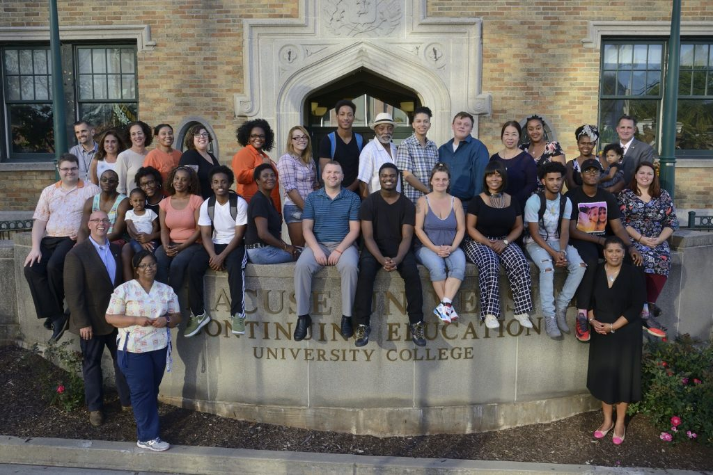 4190be83c15c group of students sitting and standing in front of University College. This  year marks the ...