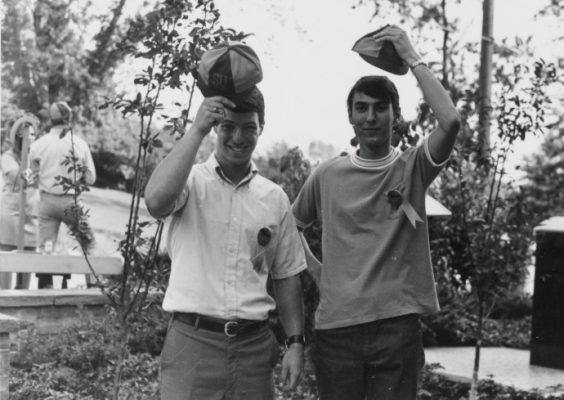 Two students holding hats over their heads.