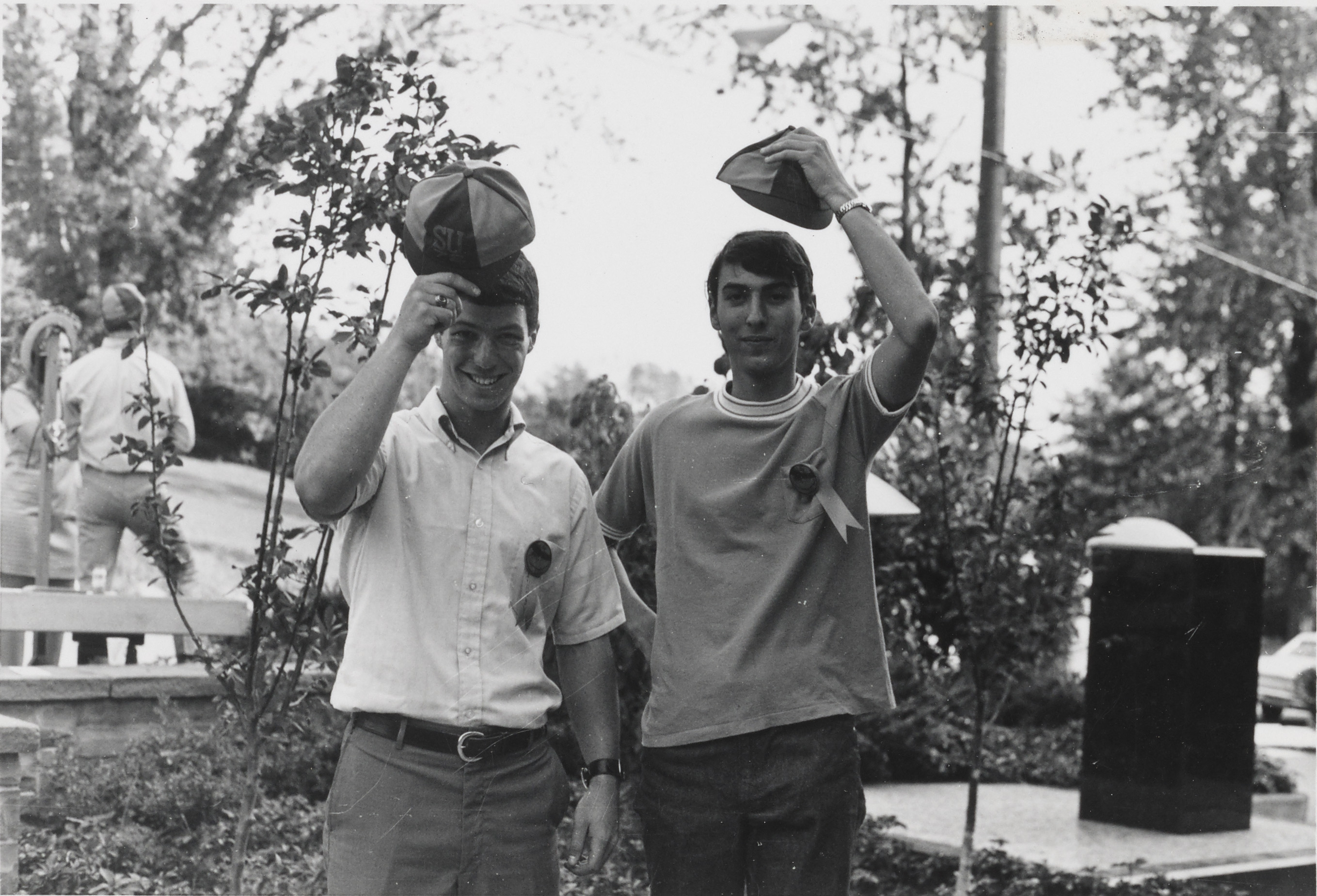 Two male students holding hats.