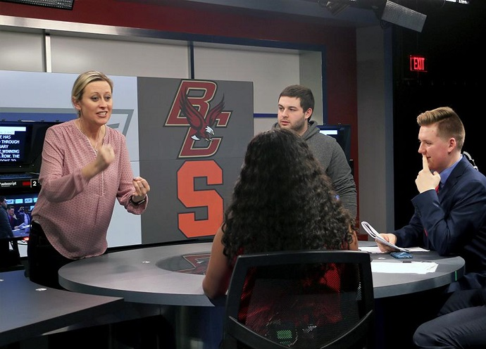 woman talking to students at anchor desk