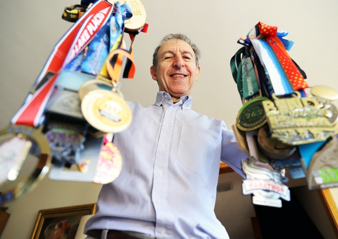 man holds up a plethora of athletic medals