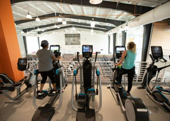 two people exercising on elliptical machines