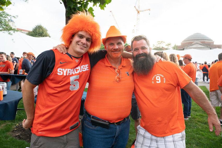 three men standing in field at tailgate