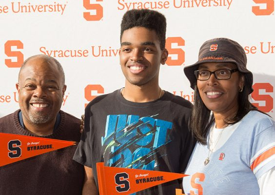 student with parents in front of Syracuse University backdrop
