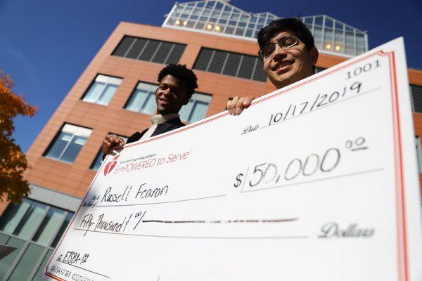students hold large award check