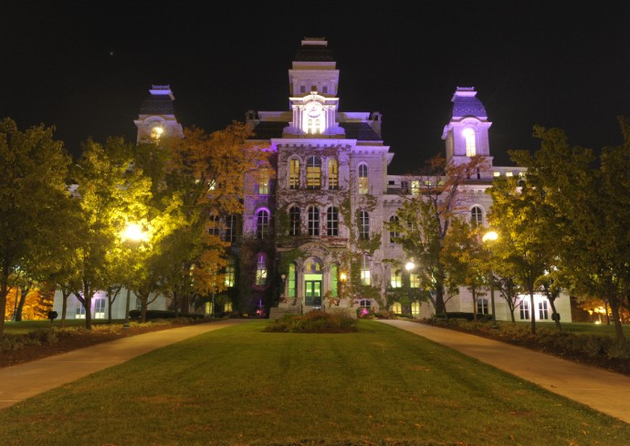 shot of the Hall of Languages at Syracuse University illuminated by purple light