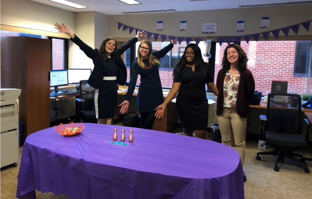four women in office space with purple decorations