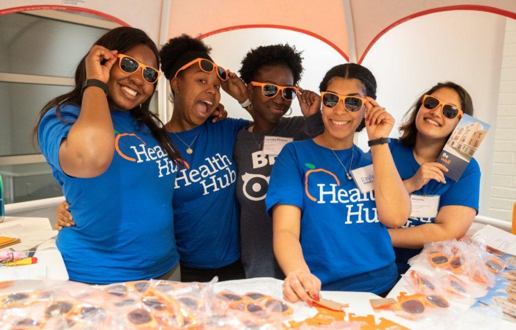 volunteers wearing orange sunglasses on quad