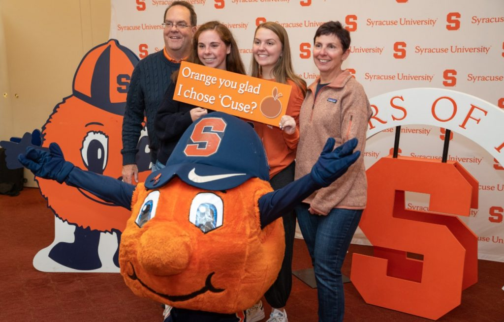 family poses with Otto in front of Syracuse University backdrop