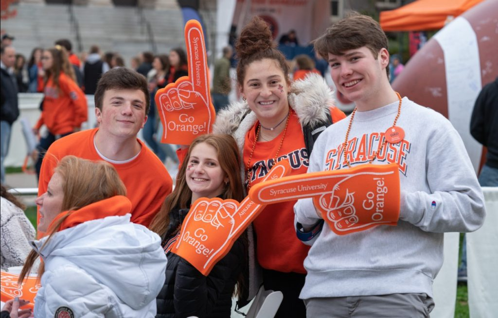 group of four with orange foam fingers at football tailgate