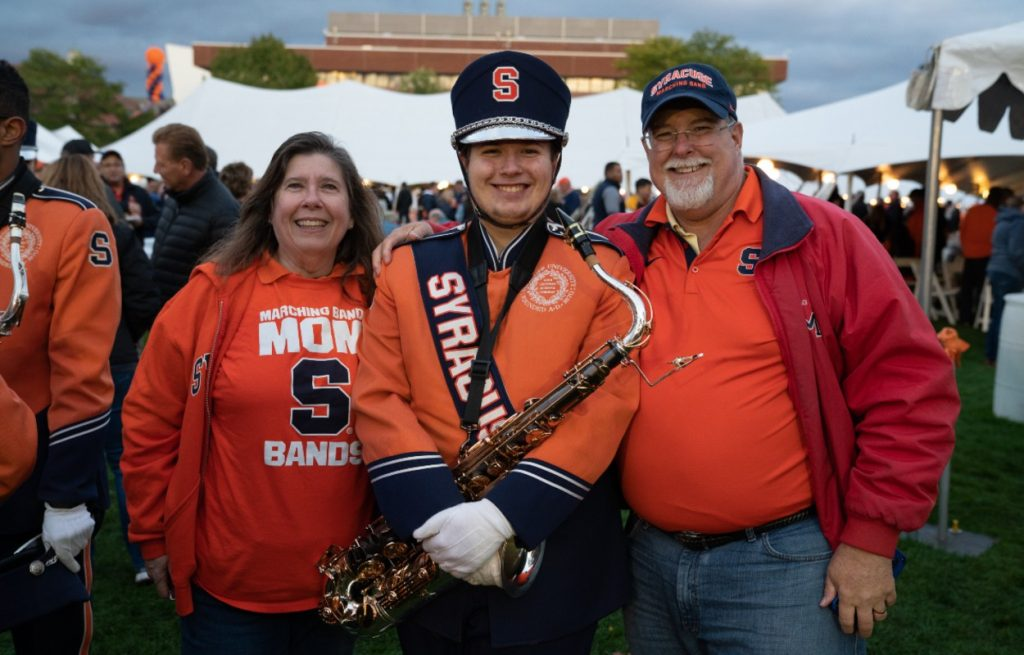 two parents pose with marching band saxophonist