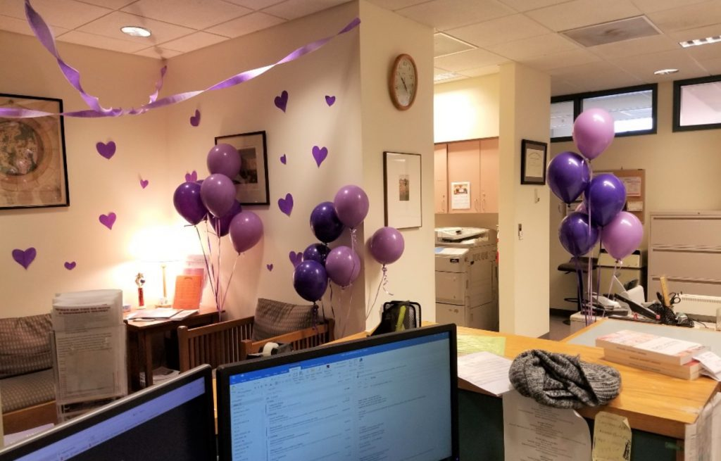 purple balloons and hearts adorn the wall of an office