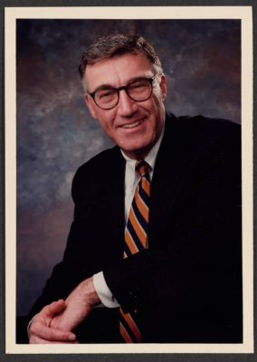 formal headshot of man with glasses