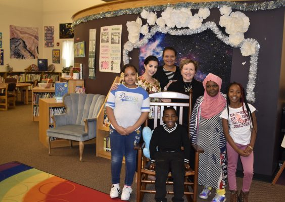 A group of adult and children smile as they surround a rocking chair in a library.