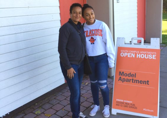 A mother and daughter stand outside the front door of an apartment. There is an open house sign signaling a model apartment next to them.