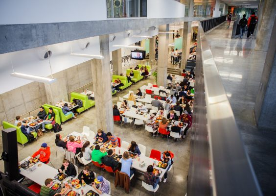 An overhead shot of students eating in a dining hall.