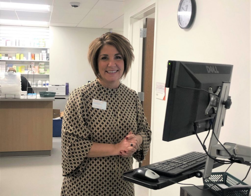 woman pharmacist standing in front of computer