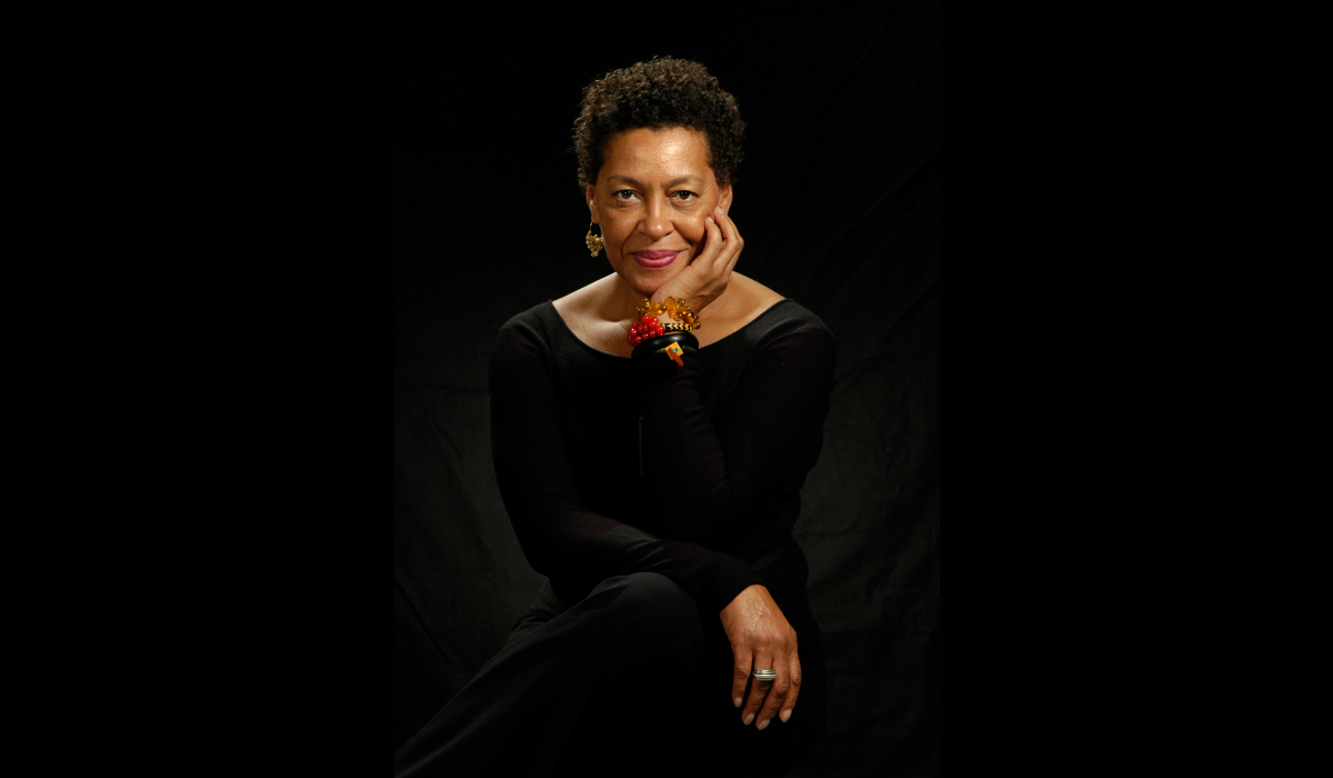 African American woman in black dress posing in front of a black background