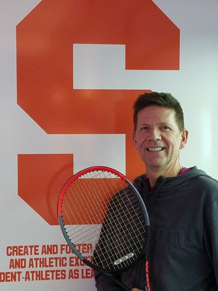 man posing with tennis racquet in front of Syracuse emblem