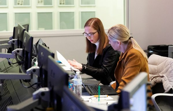 two women working together at production desk