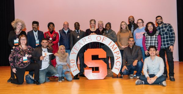 """A large group of men and women sit and stand on a stage. They are surrounding the Syracuse block S. """"150 Years of Impact"""" surrounds the S."""