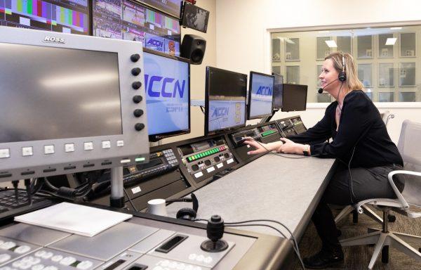 Female broadcaster sitting at desk