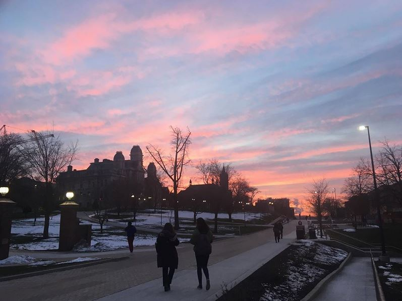 people walking on campus at dusk